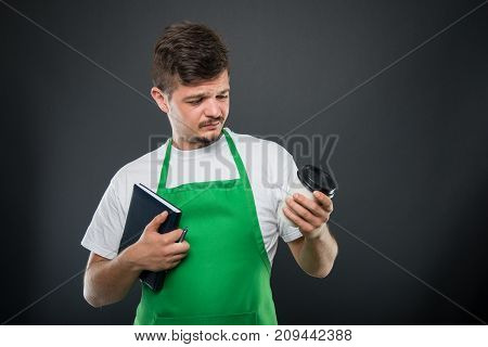 Portrait Of Supermarket Employer Holding Agenda Looking At Coffee