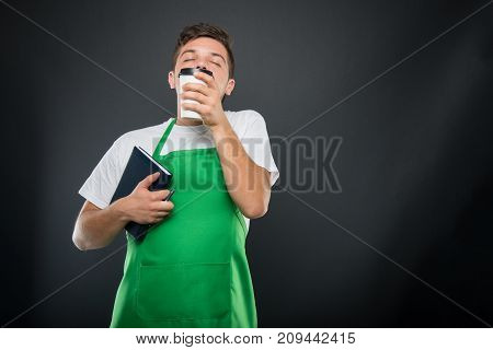 Portrait Of Supermarket Employer Holding Agenda Smelling Coffee