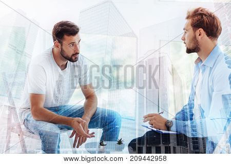 Endless problems. Good looking bearded man talking to psychiatrist while the doctor explaining possible solutions and giving pieces of advice