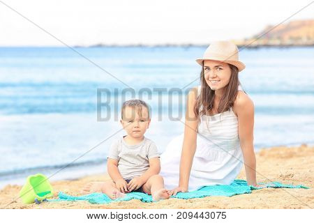 Happy mother with little son on beach