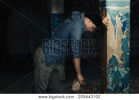 Hopeless man with bottle of alcohol in abandoned building