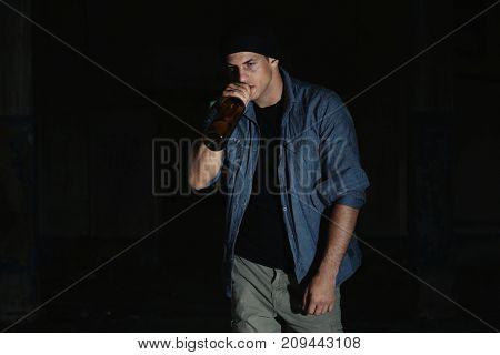 Man drinking alcohol on dark background