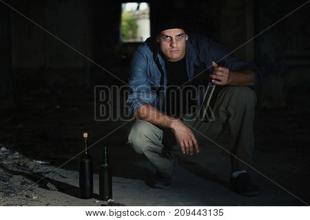 Man sitting with bottle of alcohol in abandoned building
