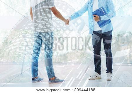 Many thanks. Close up of professional psychiatrist and grateful patient shaking hands while standing in front of each other