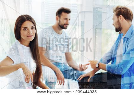 Pleased with day. Young positive woman sitting on the chair while her friends having discussion and expressing interest