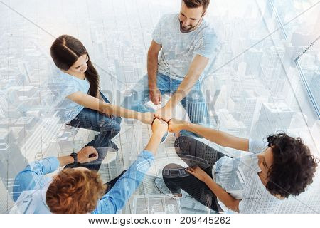 Diligent team. Top view of pleasant coworkers keeping fists together while smiling and expressing cheer