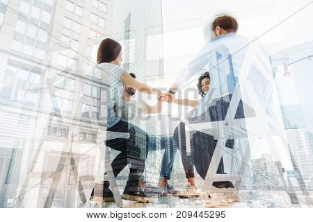 Being mentally healthy. Group of positive friends having psychological appointment while sitting and keeping fists together