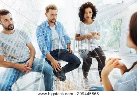 Having problems. Attentive patients sitting in front of psychologist while being serious
