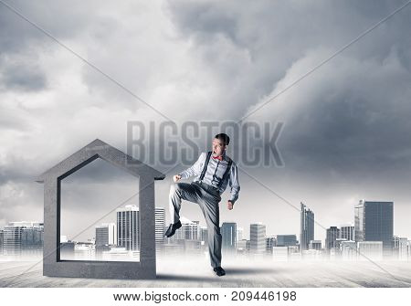 Determined businessman going to break with leg house concrete figure