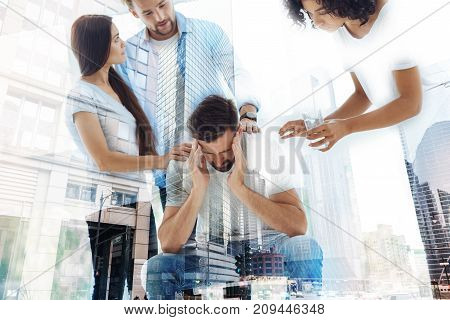 Need psychological appointment. Waist up of depressed bearded man touching his head with both hands while his friends calming him down