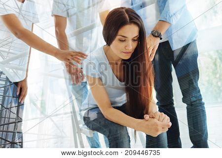 In troubles. Young long haired woman sitting on the chair and being displeased while her friends supporting her