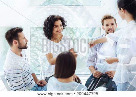 Expressing interest. Positive pleasant colleagues sitting in psychologists office while doing exercises on sheets of paper