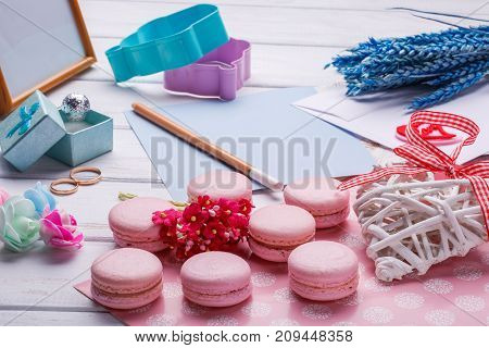 Pink macaroons. Wedding subject. wedding rings. postcard with pencil over white wooden background