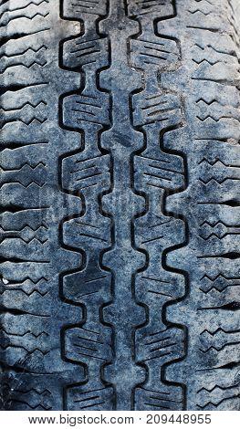 Texture of black wide combine harvester tire. Vertical orientation.