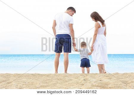 Happy couple with little son on beach