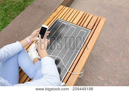 Young woman charging mobile phone on bench with solar panel