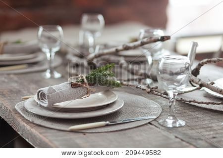 Rustic Christmas served wooden table with vintage silverware, candles and fir twigs. New Year Celebration, Christmas dinner served in loft interior.