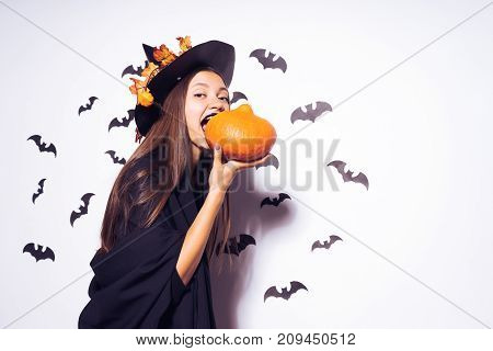The Halloween witch with long hair tries to bite off a pumpkin. A nice girl dressed in a black suit is going to a party. Against the background of bats. Wide Halloween party art design