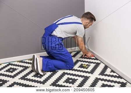 Male worker fitting carpet on floor indoors