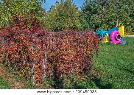 Remnants of industrial machinery painted in bright colors and set in autumn nature.