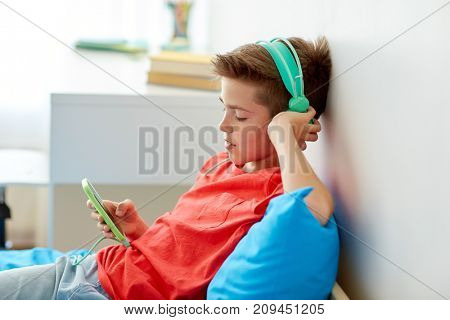 children, technology and people concept - happy smiling boy with smartphone and headphones listening to music at home
