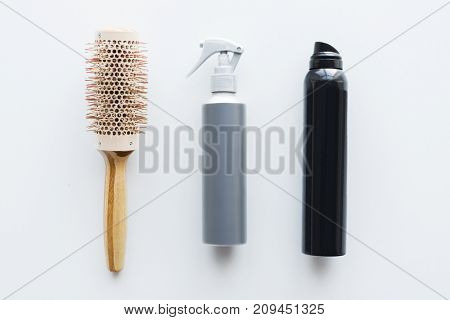hair tools, beauty and hairdressing concept - hot styling sprays and curling brush on white background