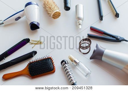 hair tools, beauty and hairdressing concept - hairdryers, irons, hot styling sprays and brushes on white background