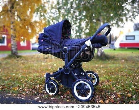 beautiful Baby carriage in colorful autumn street