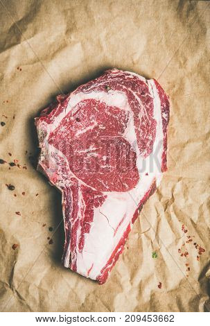 Flat-lay of raw uncooked prime beef meat dry-aged steak rib-eye on bone with seasoning on craft paper background, top view, copy space. Meat high-protein dinner concept