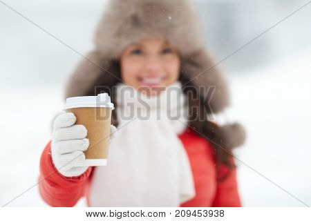 people, hot drinks and leisure concept - happy woman with disposable paper coffee cup hat outdoors in winter