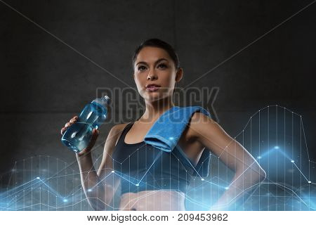 fitness, sport, training, drink and lifestyle concept - woman with towel drinking water from bottle in gym