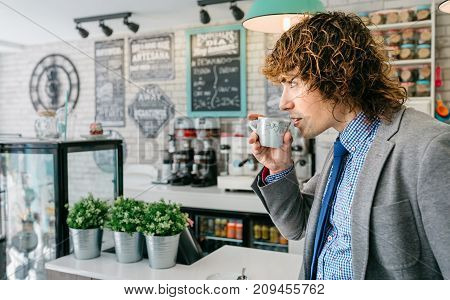 Businessman drinking coffee standing in the bar