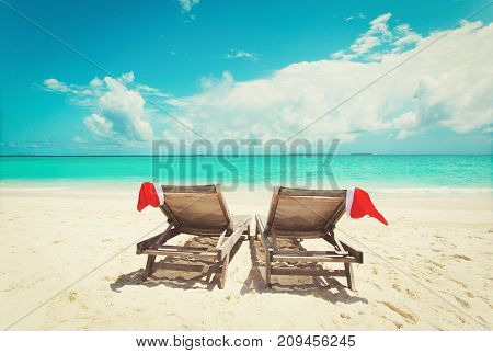 Christmas on beach -chair lounges with Santa hats at sea beach