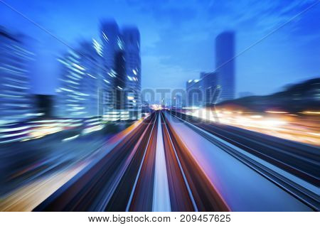 High speed train passing in between Kuala Lumpur City during dusk hour. Focus on the rail road.