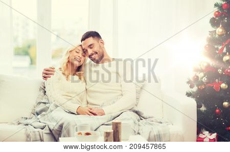 family, christmas, holidays, love and people concept - happy couple covered with plaid sitting on sofa at home