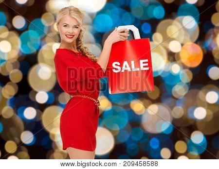 sale, christmas and people concept - smiling woman in red dress with shopping bag over lights background