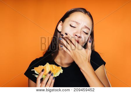 the hungry girl eats her hamburger. The girl licks her fingers. Very tasty food, isolated on an orange background