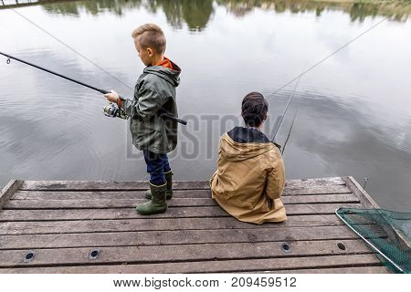 Father And Son Fishing With Rods