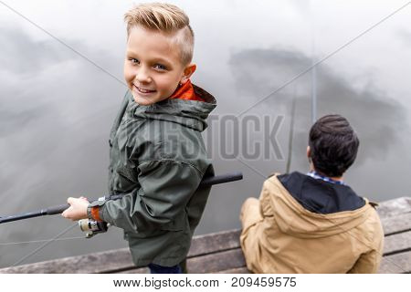 father and son fishing with rods on wooden pier at lake