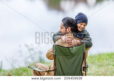Father And Son Hugging At Lake