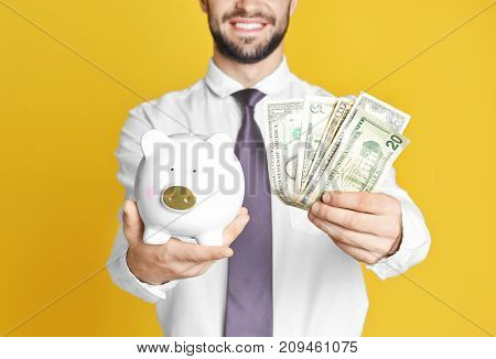 Young man with piggy bank and banknotes on color background