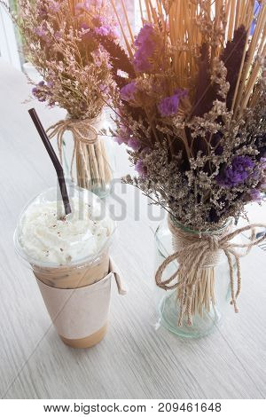 High angle view of iced coffee and whipping cream decoration with dried flowers