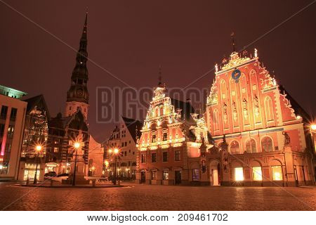 Riga Latvia. House of the Blackheads and Cathedral in the old town of Riga Latvia. Town square at night.