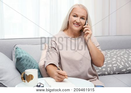 Senior woman speaking on cell phone at home