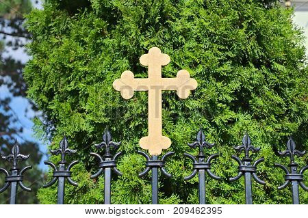 Metal cross on monastery fence, in front of tree