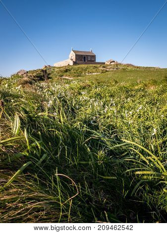 St. Nicholas chapel sitting on top of the hilly peninsula which juts out of the Cornish fishing village of St. Ives in th English West Country.