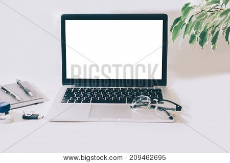Laptop mock-up and office supplies on white table
