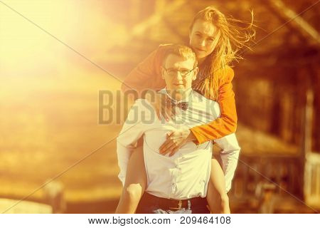 Happy Man Carrying His Girlfriend On The Back On On The Bridge Over The River. Vintage Tone