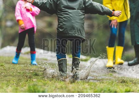 Kid Jumping In Muddy Puddle