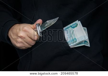 A Criminal With A Knife In His Hand And Russian Money In Your Pocket.